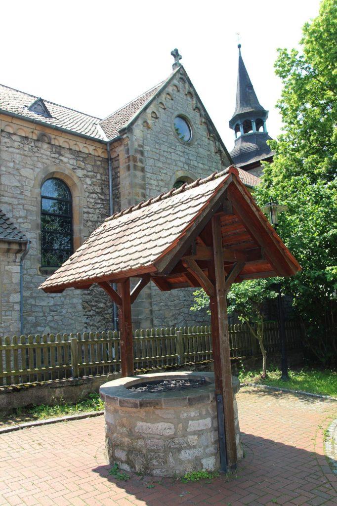Brunnen am Dorfplatz mit Blick auf die Kirche
